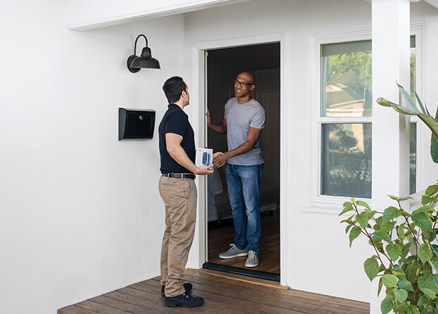 technician at customer's home about to install smart doorbell